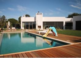 Casa branca com janelas de alumínio, piscina, escorrega, relva e chão em madeira