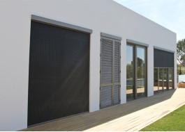 Casa branca com portas deslizantes em alumínio, chão em madeira e zipscreen