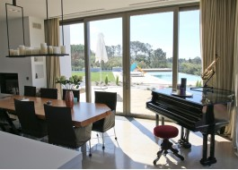 White house interior with aluminum sliding door, pool, water slide, piano and wooden table