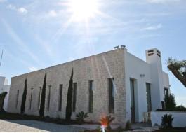 Casa branca com portas e janelas de alumínio e árvores