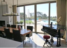 Interior de casa branca com porta deslizante em alumínio, piscina, escorrega, piano e mesa de madeira